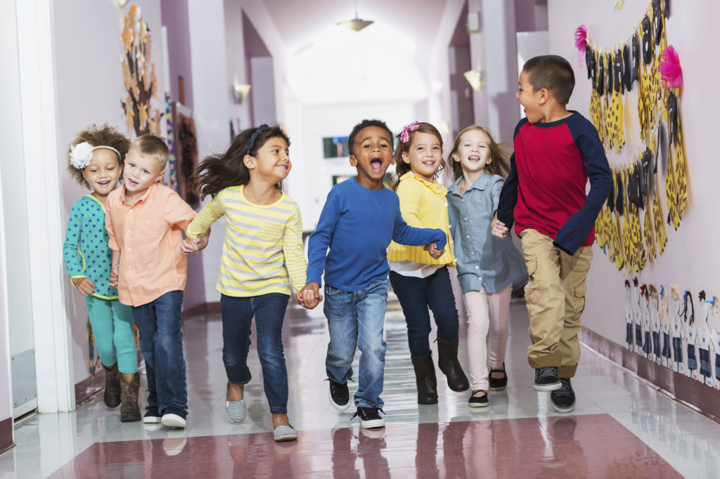 A multi-ethnic group of seven children holding hands, running down their school hallway, laughing and shouting, looking at the camera. They are in kindergarten or preschool.